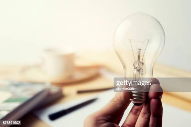 hand holding incandescent lighting bulb on wooden workspace table - incandescent bulb fotografías e imágenes de stock