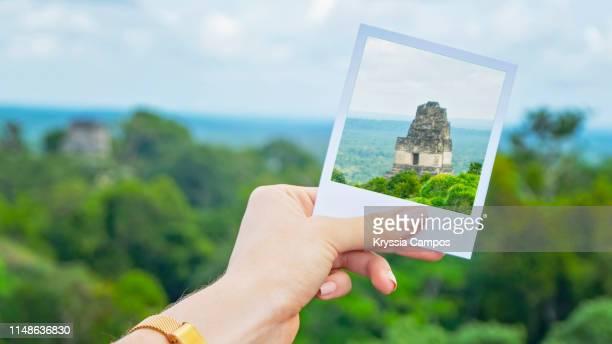 hand holding instant photo of a temple in tikal - guatemala - archäologie stock-fotos und bilder