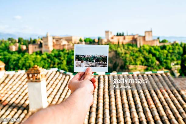 hand holding instant photo of the alhambra, granada - granada spain stock pictures, royalty-free photos & images