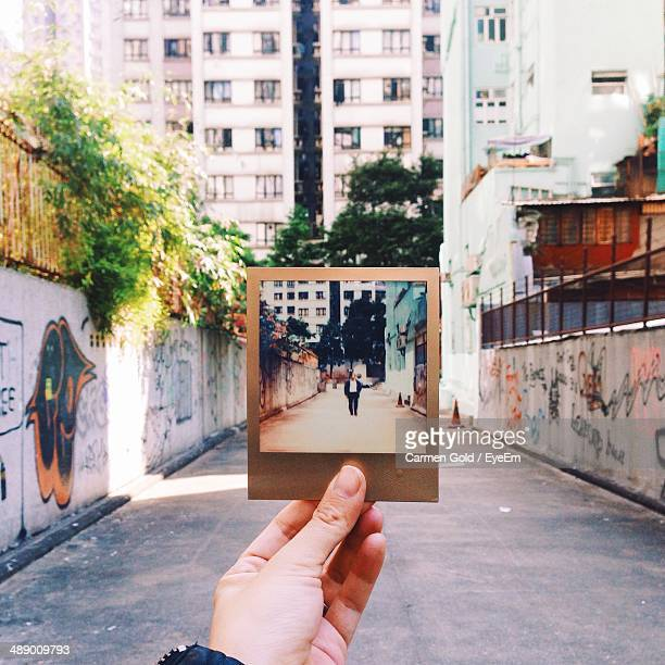 Hand holding instant photo picture frame on street