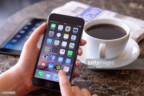 mano agarrando iphone 6 plus - spotify fotografías e imágenes de stock