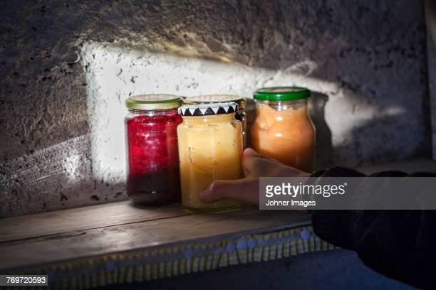 Hand holding jar of preserves