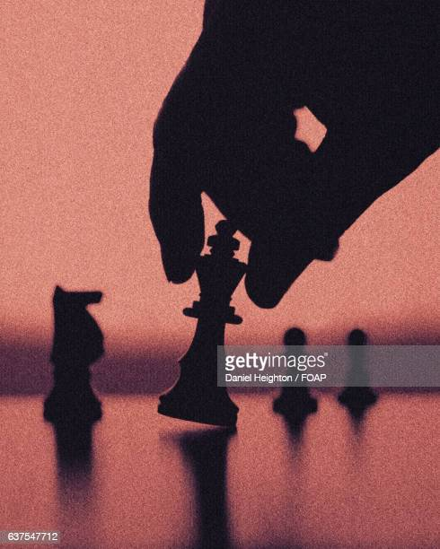 Hand holding King chess piece