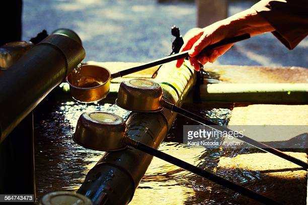 hand holding ladle at water basin - bamboo dipper stock photos and pictures