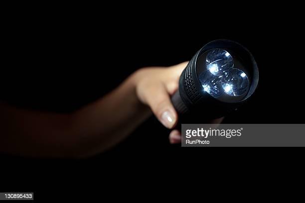 Hand holding LED flashlight,hand close-up
