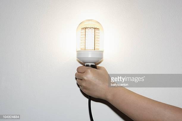 Hand Holding LED Light Bulb.