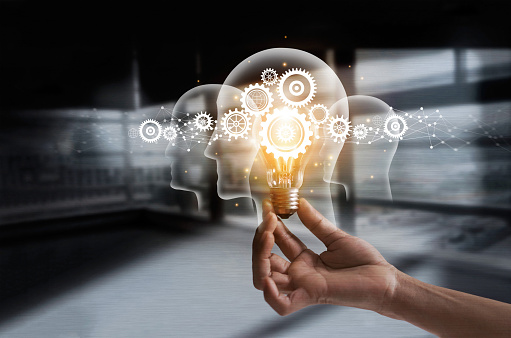Hand holding light bulb and cog inside. Idea and imagination. Creative and inspiration. Innovation gears icon with network connection on human heads on metal texture background. Innovative technology in science and industrial concept 962071696