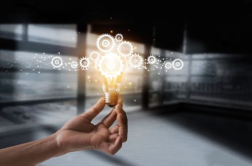 Hand holding light bulb and cog inside. Idea and imagination. Creative and inspiration. Innovation gears icon with network connection on metal texture background. Innovative technology in science and industrial concept 962094570