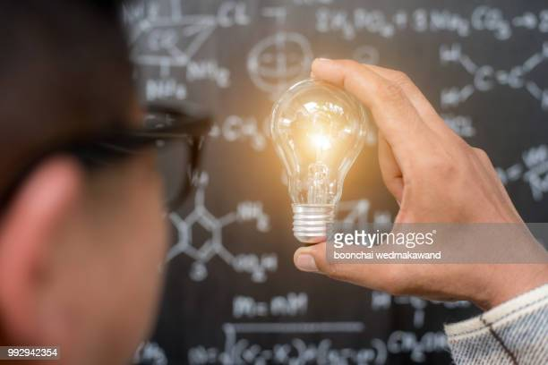 hand holding light bulb on blackboard background - signo de más fotografías e imágenes de stock