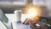 Hand holding light bulb with innovative and creativity are keys to success. Concept knowledge leads to ideas and inspiration.