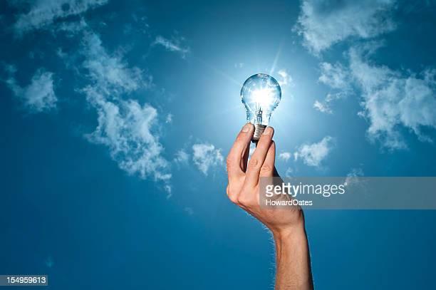 hand holding lightbulb to the sun