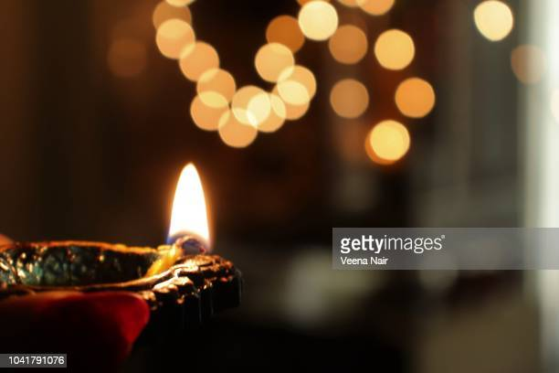 hand holding lit clay diya against bokeh background/diwali festival - diwali decoration stock pictures, royalty-free photos & images
