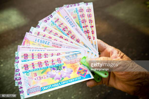 hand holding lottery ticket vietnam - sweepstakes stock photos and pictures