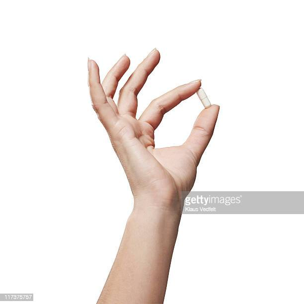 hand holding medicine capsule - mano umana foto e immagini stock