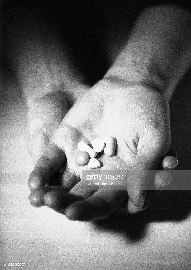 Hand holding medicine capsules in palm, B&W : Stockfoto