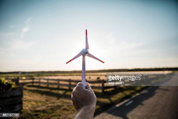 hand holding miniature wind turbine - responsibility stock pictures, royalty-free photos & images