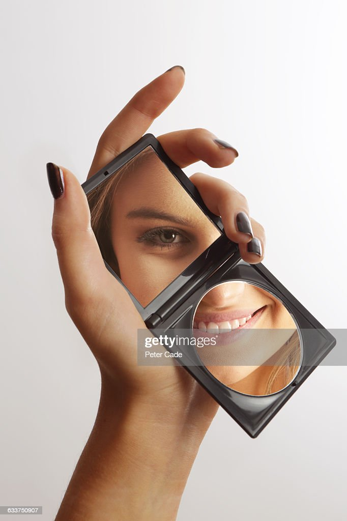 hand holding mirror reflecting womans face stock photo hand o44 hand