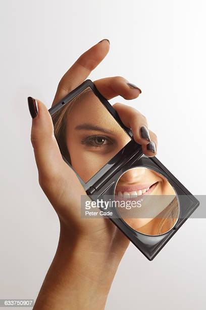 Hand holding mirror reflecting womans face