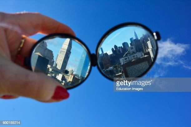 Hand Holding Mirrored Glasses with City Reflection