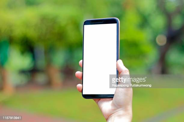 hand holding mobile or smart phone with blank screen and making selfie in the garden - black hand holding phone stock pictures, royalty-free photos & images