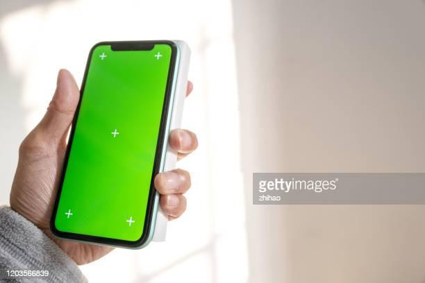 hand holding mobile phone and power bank - チャージする ストックフォトと画像