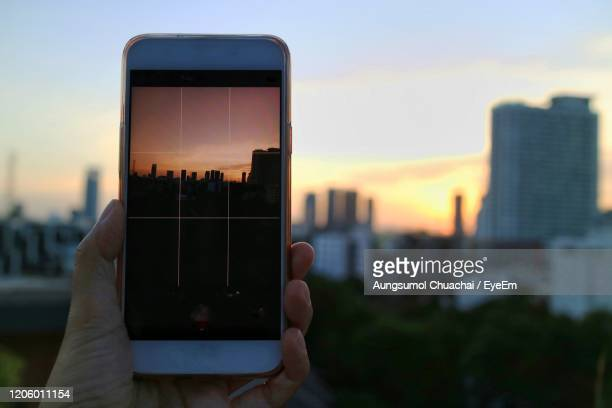 a hand holding mobile phone and take a photo sunset paradise with blue sky and cloud in big city. - aungsumol stock pictures, royalty-free photos & images