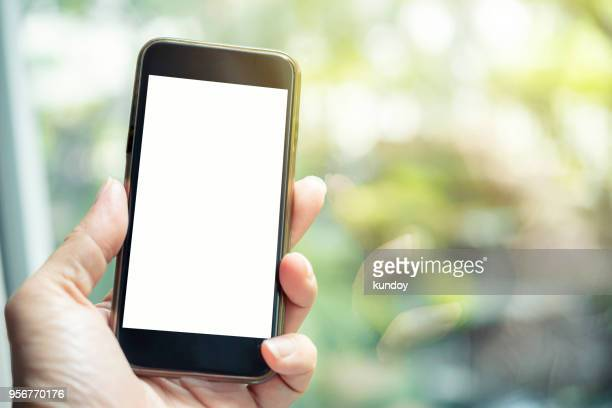 hand holding mobile with empty screen for background. mobile mock up for advertising. - sms'en stockfoto's en -beelden