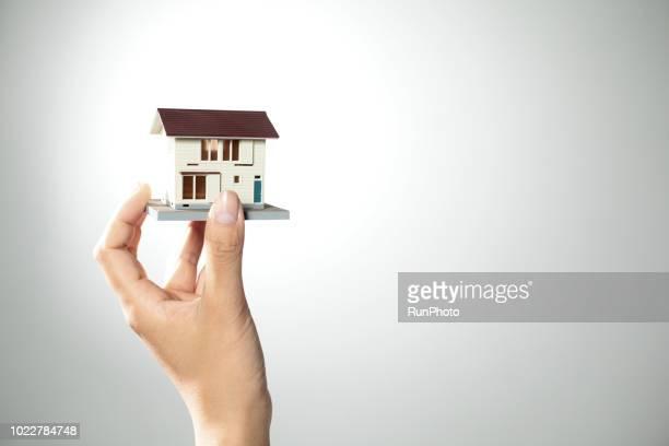 hand holding model house - bens imóveis imagens e fotografias de stock