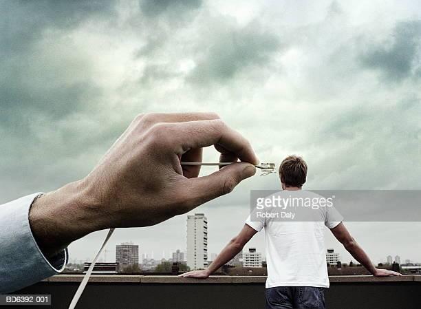 Hand holding modem plug, man against city skyline in background