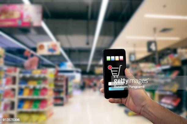 hand holding modern smartphone online shopping application on device screen with background blurred - marketing icons stock photos and pictures