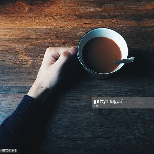 Hand holding mug of hot chocolate on wooden table