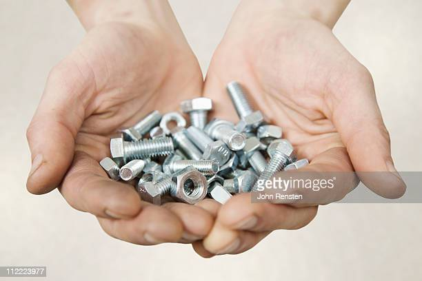 Hand holding nuts and bolts