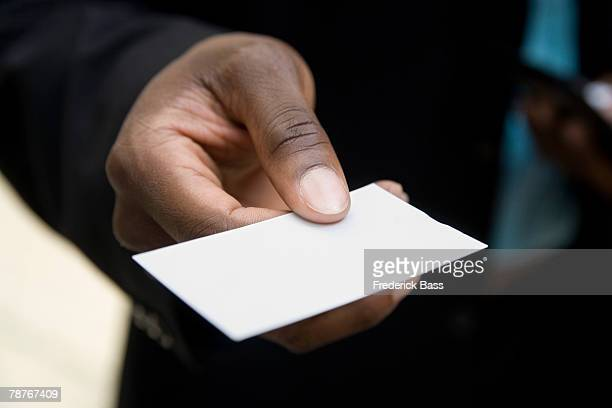 hand holding out a blank business card - business cards stock photos and pictures