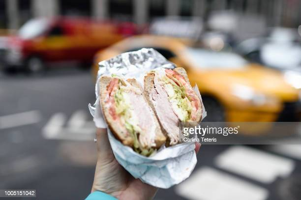 hand holding out a deli sandwich in new york city - convenience store stock photos and pictures