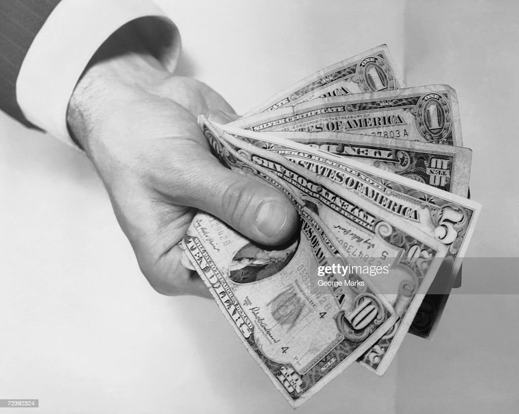 Hand holding out money : News Photo