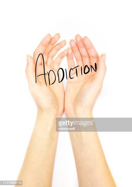 hand holding out palm straight with addiction - addiction stock pictures, royalty-free photos & images