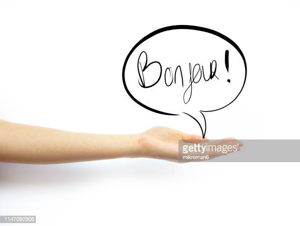 hand holding out palm straight with speech bubble saying bonjur - speech stock pictures, royalty-free photos & images