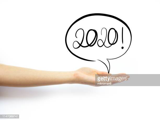 hand holding out palm straight with speech bubble with 2020 new year - new year's day stock pictures, royalty-free photos & images