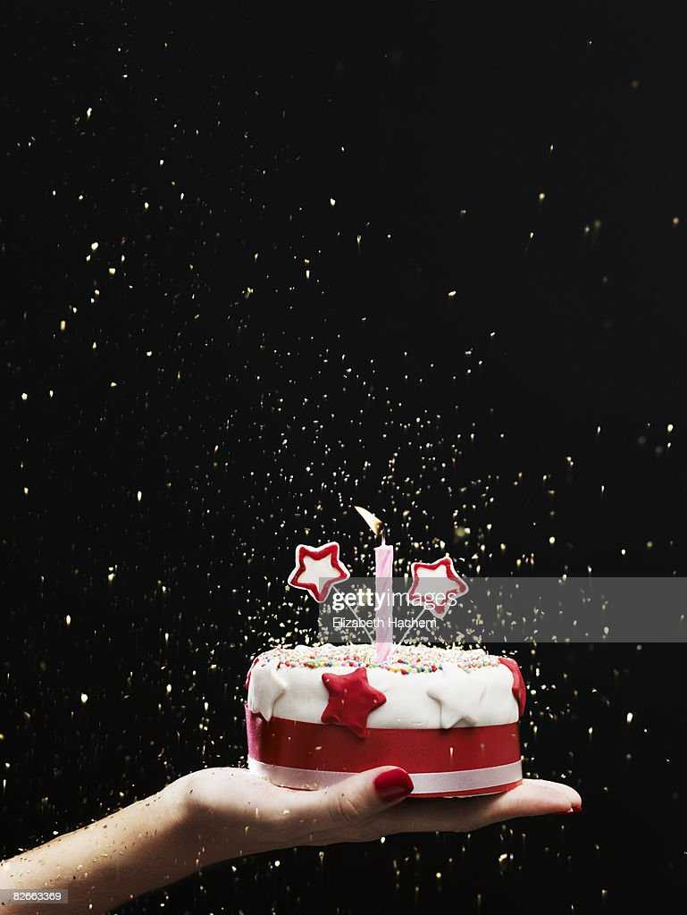 Hand holding out small cake : Stock Photo