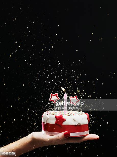 hand holding out small cake - birthday cake stock pictures, royalty-free photos & images