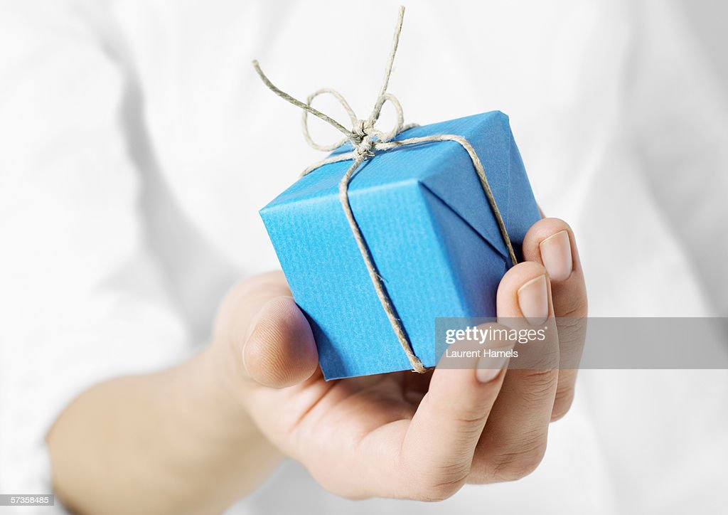 Hand holding out small package : Stock-Foto
