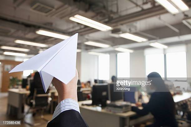 Hand holding paper airplane in office