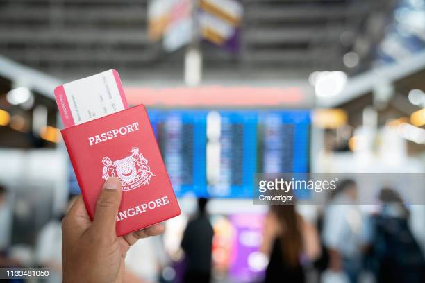 Hand holding passports and boarding pass in the international airport.