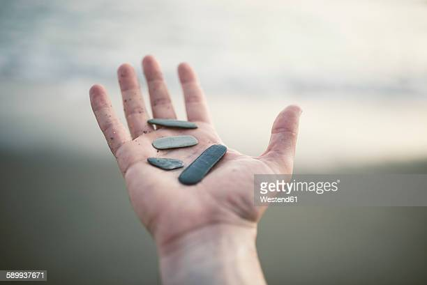 Hand holding pebbles