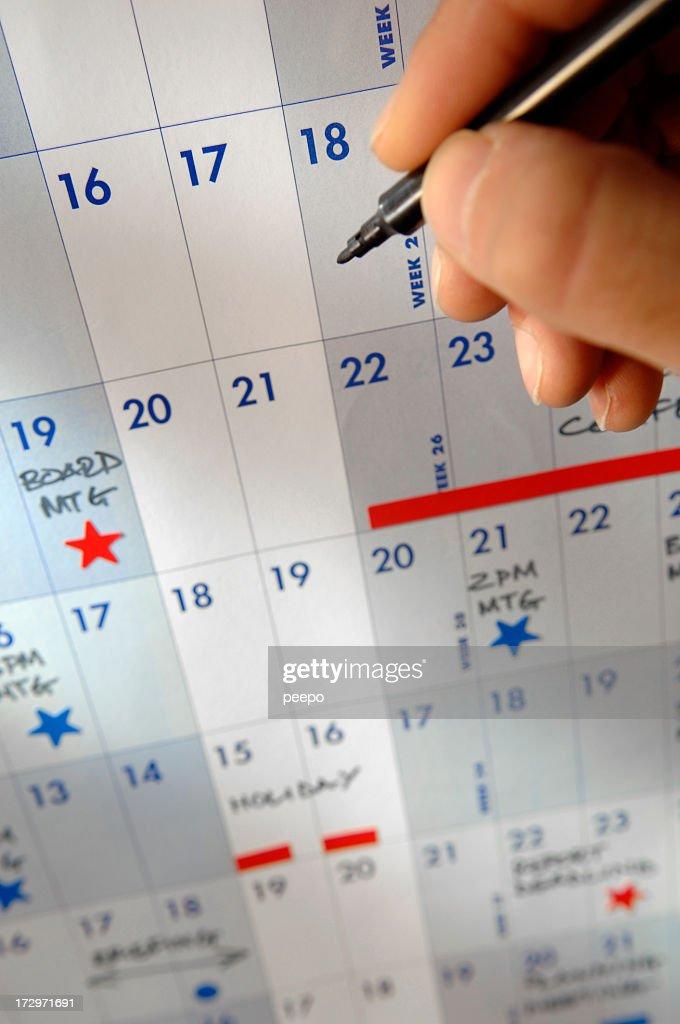 Hand Holding Pen Over Calendar : Stock Photo
