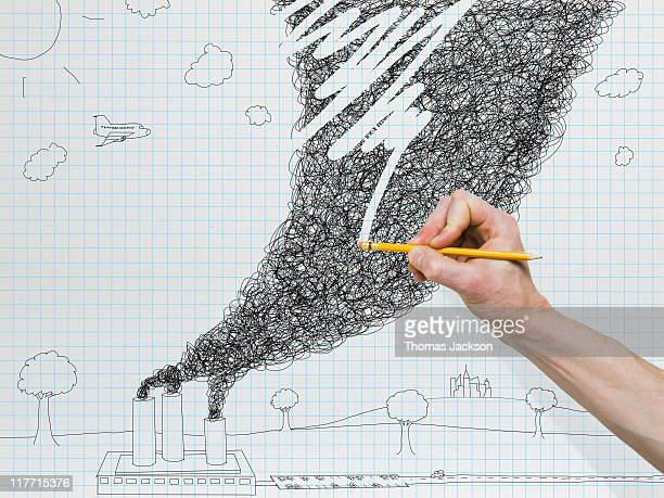 Hand holding pencil erasing pollution