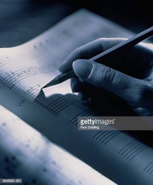 Hand holding pencil, transcribing musical score, close-up, B&W