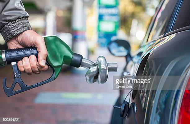 Hand holding petrol nozzle with spout in a knot