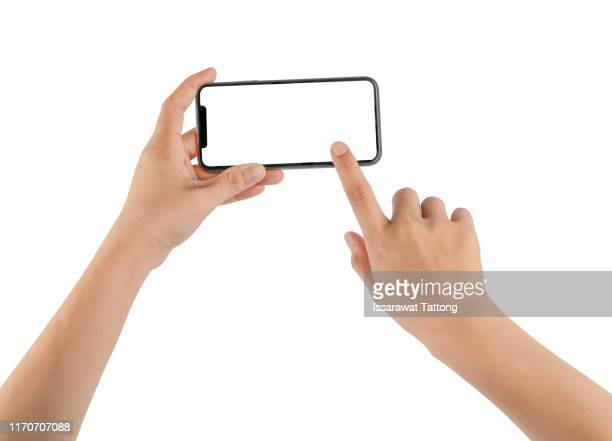 hand holding phone mobile and touching screen isolated on white background - menschliches körperteil stock-fotos und bilder