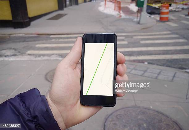 Hand holding phone with generic GPS directions